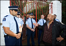Protest organiser Alan Taione talks to a Tongan policeman outside the Tongan royal family residence in Epsom. Picture / Paul Estcourt