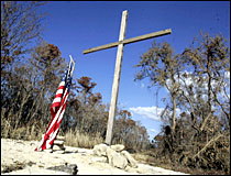 A cross and the American flag stand where a house once stood and its residents died from Hurricane Katrina. Picture / Reuters