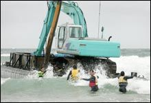 Workers try to secure a barge with digger aboard being used to build a surf reef in Mt Maunganui. Picture / Alan Gibson