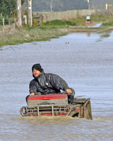 Farmer Steffen Akkerman negotiates a flooded road in Whangaehu, near Wanganui, in July. Photo / Anthony Phelps