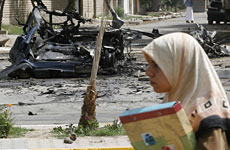 A student walks past the wreckage of a vehicle used in a car bomb attack in Baghdad. Photo