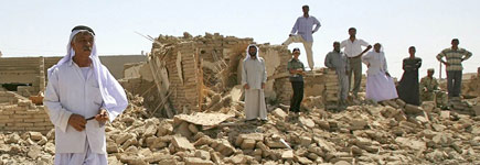 Men stand at the site of a suicide bomb attack in the village of Kahtaniya. Photo / Reuters
