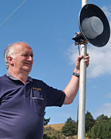 Ken Jones with his homemade wok TV transmitter. Photo / Oamaru Mail