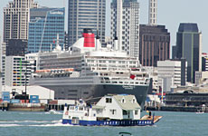 A barge carrying a house passes the Queen Mary harboured at Auckland.  Photo / Janna Dixon