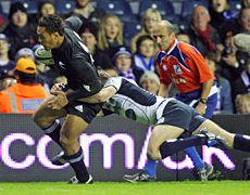 Anthony Tuitavake goes in for the All Blacks' opening try against Scotland at Murrayfield this morning. Photo / AP