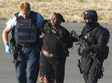 The woman who stabbed two pilots on an Eagle Air flight is escorted by armed police. Photo / Reuters