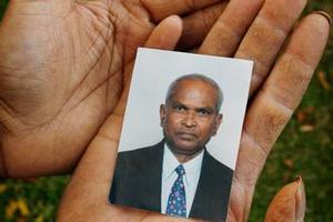 A relative holds a photo of Jasmatbhai Patel. Photo / Greg Bowker
