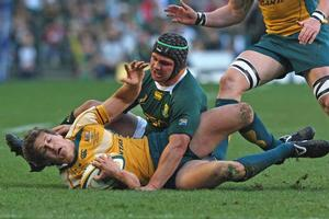 Springbok flanker Heinrich Brussow tackles Luke Burgess of the Wallabies during this morning's Tri-Nations test in Cape Town. Photo / Getty Images