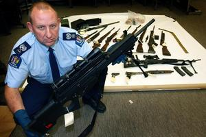 Senior Sergeant Dave Archibald shows firearms found at a BOP house in July. Photo / Sarah Ivey