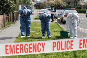 Police examine the scene at the Wainoni house where the bodies of two women were found buried. Photo / Simon Baker