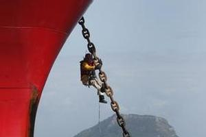Greenpeace protester Dom Zapata hangs from the anchor chain of the East Ambition. Photo / Alan Gibson