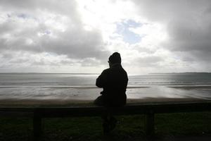 Ghanshyan Patel, sits near his home at Red Beach, Whangaparoa and watches for the tsunami to hit. Photo / Glenn Jeffrey
