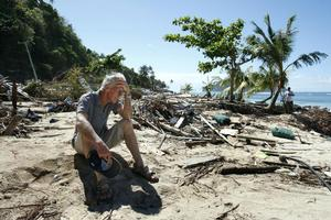 Andy Belcher sits among the devastation on a beach in southeast Samoa. Photo / Brett Phibbs