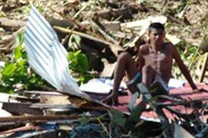 A Samoan resident sits on debris left behind by the tsunami. Photo / Cherelle Jackson