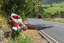 Flowers mark the spot on Peak Rd, Helensville, where Graham Robinson was knocked off his bicycle. Police are still hunting for the driver of the white Toyota Hilux involved in the incident. Photo / Brett Phibbs