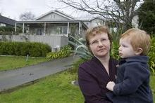 Kate Holgate and son Jack in front of a house she tried to buy in a 'part exchange' deal with her own house in Torbay. Photo / Paul Estcourt