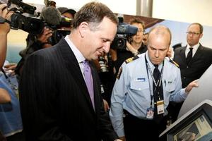 Prime Minister John Key tries his hand at the new SmartGate kiosk at Auckland Airport. Photo / NZPA