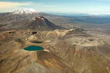 The starkly beautiful Central Plateau with the Blue Lake of Mt Tongariro, Mt Ngauruhoe and snow-capped Mt Ruapehu. Photo / Greg Bowker