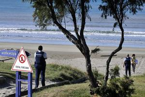 Police warn tsunami watchers at Midway Beach in Gisborne to move after water was sucked out of the bay. Photo / NZPA