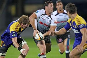 Riaan Swanepoel of the Sharks offloads the ball as he is tackled by Adam Thomson of the Highlanders. Photo / Getty Images