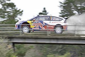 Sebastien Loeb's car spews a cloud of smoke shortly after it struck a railway overbridge. Photo / NZPA