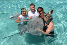 Our guide Taaroa (second from right), tourists and a very friendly ray. Photo / Jill Worrall
