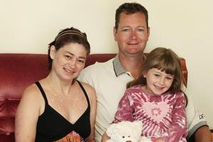 Angela and Alan Symes are seen at home with daughter Caitlin, 6. Photo / Christine Cornege