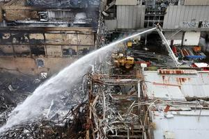 Firefighters dampen down hot spots at the Southdown freezing works. Photo / NZPA