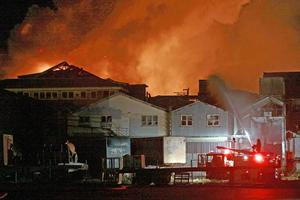 Thirty fire appliances and more than 120 firefighters are battling the fire which broke out in the old Southdown freezing works. Photo / NZPA
