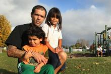 Ex-gang member Paku Waara with his children Exodus (left) and Teaotaihi at the Cutler Crescent reserve. Photo / Alan Gibson