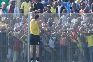 Striker Rory Fallon passes a T-shirt to fans watching an All Whites training session in Johannesburg. Photo / Brett Phibbs