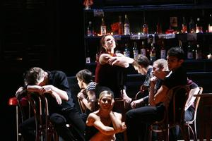 Pieter Symonds as Carmen seated on table at Bar Pastia with her friends around her. Photo / Maarten Holl.