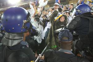 New Zealand fans are forced out of the Peter Mokaba Stadium by South African riot police. Photo / Brett Phibbs
