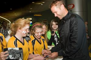 Mark Paston signs autographs for members of Massey High School Girls' First XI at Auckland Airport yesterday. Photo / Paul Estcourt