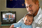 Daniel Brown, with 5-month-old Eruwera, checks out the new DVD about how to be a father. Photo / Natalie Slade
