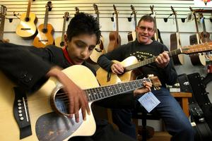 Michael Chopra tries the guitar made for him by Gary Price (rear). Photo / Alan Gibson