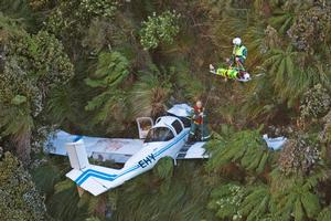 One of the injured pilots is winched up to the Square Trust helicopter from the crash site in the Pohangina Valley near Palmerston North. Photo / Mark Mitchell