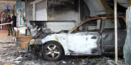 The burnt out shell of a liquor store and stolen car following a ram raid at the Northcrest shops in Manurewa, Auckland. Photo / NZPA