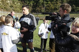 Sarah Mitchell, (11)of Waikanae, videos All Blacks first five-eighths Dan Carter as he signs autographs after their training session in Wellington earlier this month. Photo / Mark Mitchell