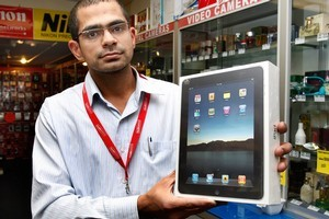Parallel Imported Queen St store manager Anshul Choudhary holds an Apple iPad, which they have been selling instore for about a month. Photo / Brett Phibbs