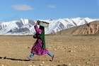 An Afghan girl walks home in the mountainous fields of Bamiyan, Afghanistan. Photo / Getty Images