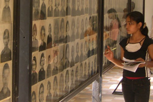 A schoolgirl looks at the faces of victims at the Tuol Sleng Genocide Museum in Cambodia. Photo / Jim Eagles
