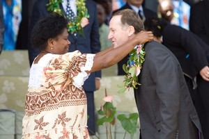 Prime Minister John Key is presented with a flower necklace for the opening ceremony of the forum. Photo / Mark Mitchell