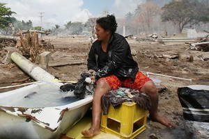 A woman washes clothes amongst the rubble after the Samoan tsunami. Photo / Greg Bowker
