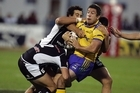 Eel Nathan Cayless (centre) is felled by the Warriors. Photo / Herald on Sunday