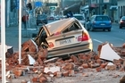 A car, destroyed by falling rubble, on Madras Street in central Christchurch. Photo / NZPA