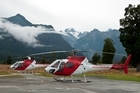 Helicopters at Fox Glacier airport with Mt Cook in the background. Photo / Luke Chapman