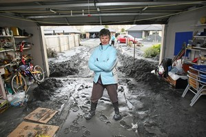 Annette Preen stands inside the garage at her destroyed home in the Christchurch suburb of Bexley. Photo / Greg Bowker