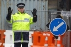 A police officer directs traffic after lights were put out by an aftershock this morning. Photo / Sarah Ivey