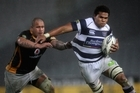 Auckland's Peter Saili is held by John Schwalger. Photo / Getty Images